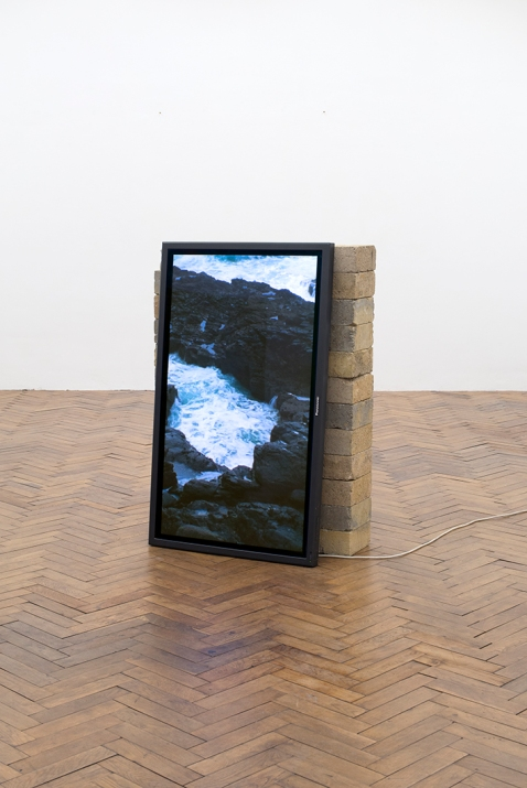 Jonathan Michael Ray, Up Against The Rocks, 2018 90x35x120cm, 16mm film (4mins, colour, no sound), HD Monitor, concrete blocks and PVC vinyl print